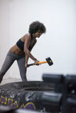 Black woman workout with hammer and tractor tire Stock Photos