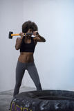 Black woman workout with hammer and tractor tire Stock Image