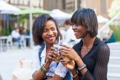Black Women in New York. Two Beautiful Black Woman Enjoying Refreshing Drinks in New York Royalty Free Stock Photography