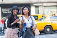 Black Women in New York. Two Beautiful Black Woman Enjoying Refreshing Drinks in New York Stock Image