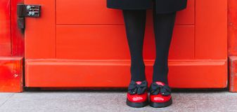 Black women`s boots. Red door and girl in red shoes royalty free stock photos