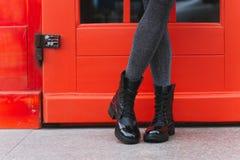 Black women`s boots. Red door and women`s legs in black boots stock photography