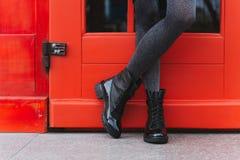 Black women`s boots. Red door and women`s legs in black boots stock images