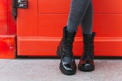 Black women`s boots. Red door and women`s legs in black boots stock image