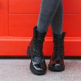 Black women`s boots. Red door and women`s legs in black boots stock photo