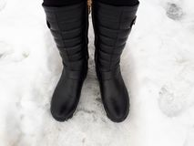 Black women`s boots in the snow stock photo