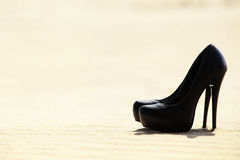 Black women's high heels are in the sand Royalty Free Stock Photos