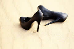 Black women's high heels are in the sand Stock Photos
