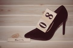 Black women& x27;s shoes by March 8. Heeled shoes and wooden calendar. Design a lovely gift. Vintage color ton stock photo