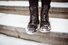 Black women's shoes. On the stone steps covered by snow in the winter royalty free stock images