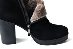 Black womens ankle boots with natural fur. Black womens ankle boots with a natural fur stock images