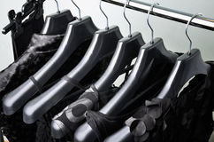 Black womens clothing hanging on the black plastic hanger top vi Stock Photos