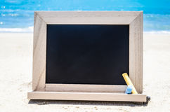 Black wood chalkboard with chalk on the sandy beach Royalty Free Stock Photography