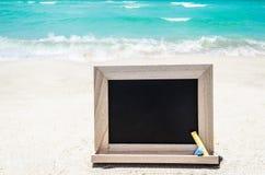 Black wood chalkboard with chalk on the sandy beach Stock Photo
