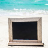 Black wood chalkboard on the sandy beach. Empty black wood chalkboard on the sandy beach near the ocean - Instagram format Stock Photography