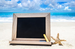 Black wood chalkboard with starfish and chalk on the sandy beach Royalty Free Stock Images