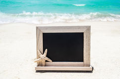 Black wood chalkboard with starfish on the sandy beach Stock Images