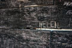Wood Carved with the word Helen. Black wood with name Helen carved into the grain stock photo