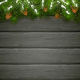 Black wooden background with Christmas fir tree branches. Christmas theme with winter decorations and pinecone, decorative spruce branches with pine cones and Royalty Free Stock Image