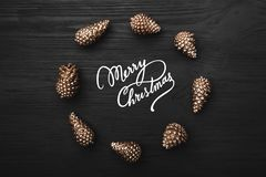 Black wooden background with the texture highlighted with golden cones in the shape of a circle on it. With Merry Christmas message. Top view Royalty Free Stock Photo