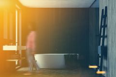 Black and wooden bathroom, white tub, girl Royalty Free Stock Image