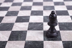 Black wooden bishop on chessboard Royalty Free Stock Image