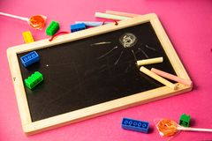 Black wooden board with crayons on a pink background royalty free stock photos