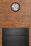 Black wooden cabinet and clock in empty room with red brick wall stock images