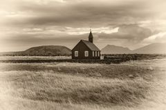 Black wooden church of Budir in Iceland. Scenery of black wooden church of Budir in Iceland with the pasture and mountains in the background. Vintage black and Royalty Free Stock Image