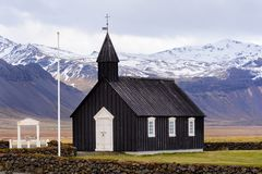 Black wooden church in Iceland against the background of the mountains. Budir Church stock image