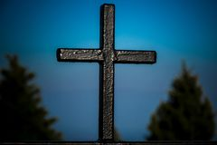 Black wooden cross against blue skies royalty free stock photography