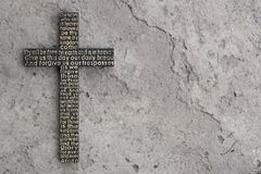 Black wooden cross with the Lord`s prayer on the grey concrete with cracks background. Royalty Free Stock Photo