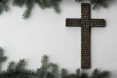 Black wooden cross with the Lord`s prayer on white wooden plank with fir tree branches background stock photography