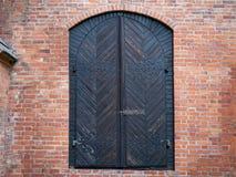 Wooden door in the brick wall. Black wooden door in the brick wall royalty free stock image