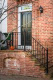 Black Wooden Front Door of a Traditional Brick House. Traditional Black Wooden Door at the Top of a Short Flight of Steps on the Front of a Old Brick House Royalty Free Stock Photo