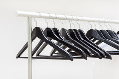 Black wooden hangers hanging on rack rail Royalty Free Stock Photos
