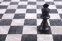 Black wooden king on chessboard Royalty Free Stock Images