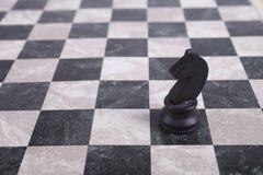 Black wooden knight on chessboard. Black wooden knight standing on chessboard Stock Image