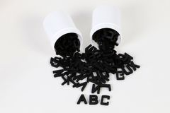 Black wooden letters with small tins. Black wooden letters are falling out of small plastic tins in the studio stock photos