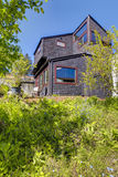 Black wooden modern house with spring backyard. Royalty Free Stock Images