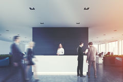 Black wooden office, white reception, people. Front view of a white reception desk standing in an open space office environment with a black wall, rows of royalty free stock photography