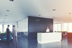 Black wooden office, white reception, side, men. Side view of a white reception desk standing in an open space office environment with a black wall, rows of Royalty Free Stock Images