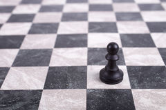 Black wooden pawn on chessboard. Black wooden pawn alone on chessboard Stock Image