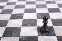 Black wooden pawn on chessboard. Black wooden pawn standing on chessboard Royalty Free Stock Images