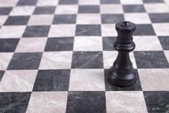 Black wooden queen on chessboard. Black wooden queen standing on chessboard Royalty Free Stock Photos