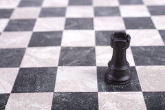 Black wooden rook on chessboard Royalty Free Stock Photos