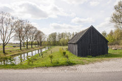 Black wooden shed near canal Royalty Free Stock Images
