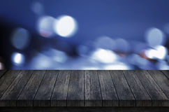 Black wooden table for presentation. Blue bokeh city lights in background Royalty Free Stock Image
