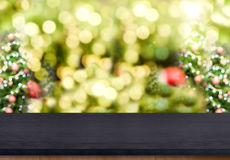 Black wooden table top with abstract blur christmas tree background with bokeh light,Holiday backdrop,Mock up for display or mont royalty free stock photo