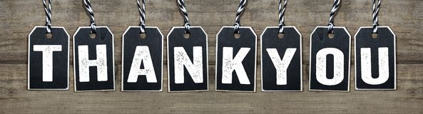 Black tags on natural wood with Thank you stock photo